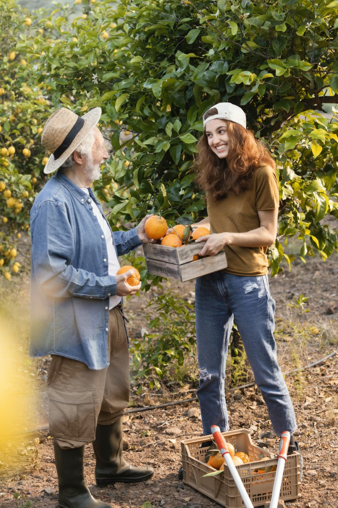 woman-helping-her-dad-get-some-oranges-from-the-trees-in-the-garden